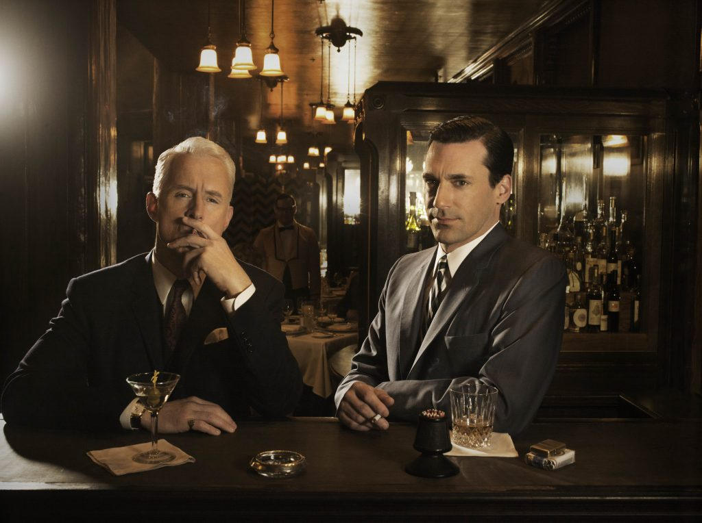 two men are smoking and drinking at a bar in dim light