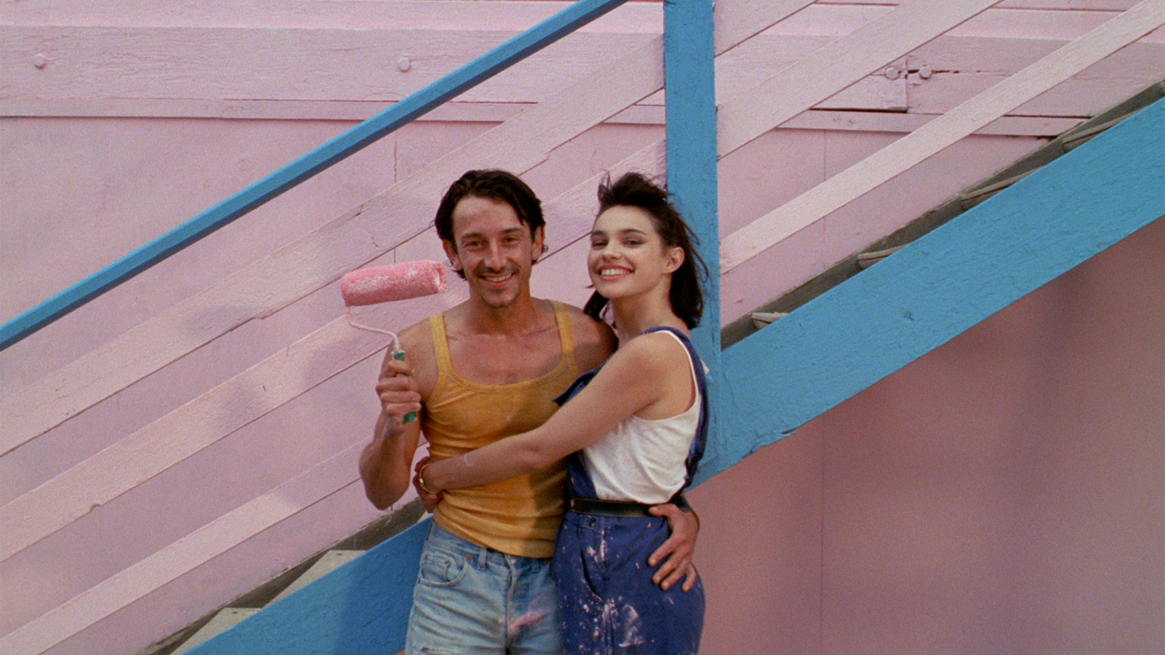 Photo of Betty and Zorg in front of a pink and blue wall, from the film Betty Blue