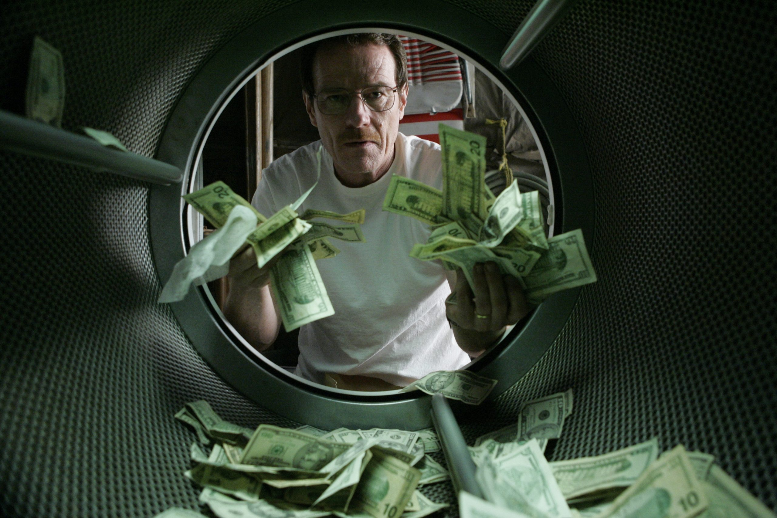 A man is standing in front of a washing machine which contains banknotes
