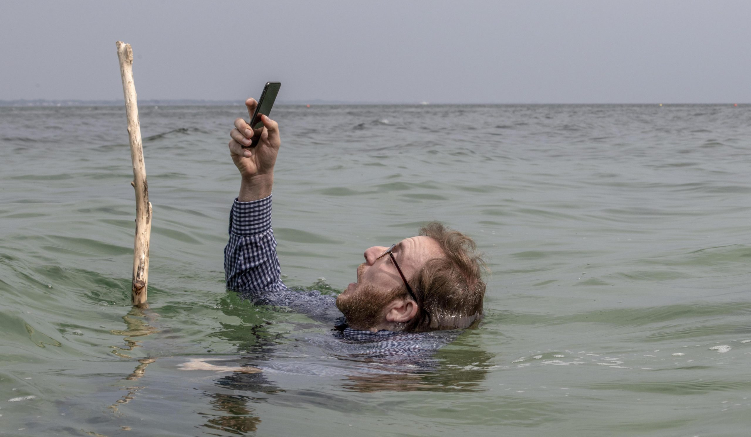 A men risks drowning while looking at his phone, in a Selfie scene