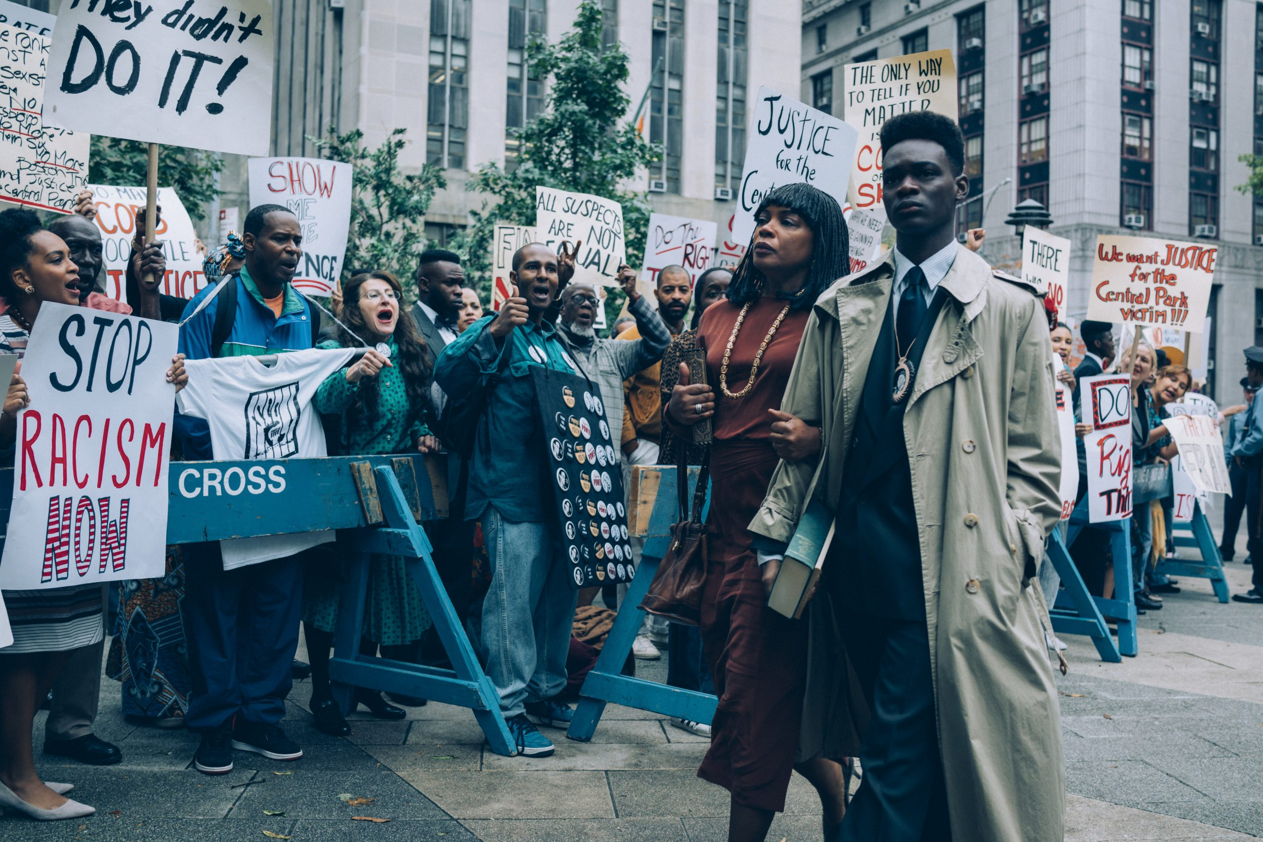A scene in When they see us: A teenager, a woman and a crowd of protesting people in the daylight