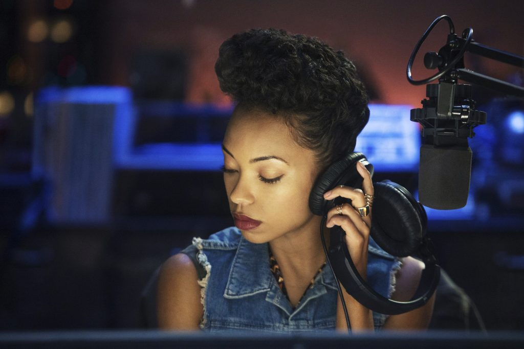 Dear white people - A black woman inside a recording studio is holding her headphones