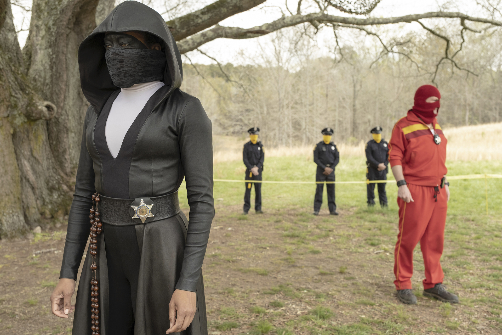 The Watchmen cast - A woman all dressed in black, a man all dressed in red and three police officers are standing inside a park