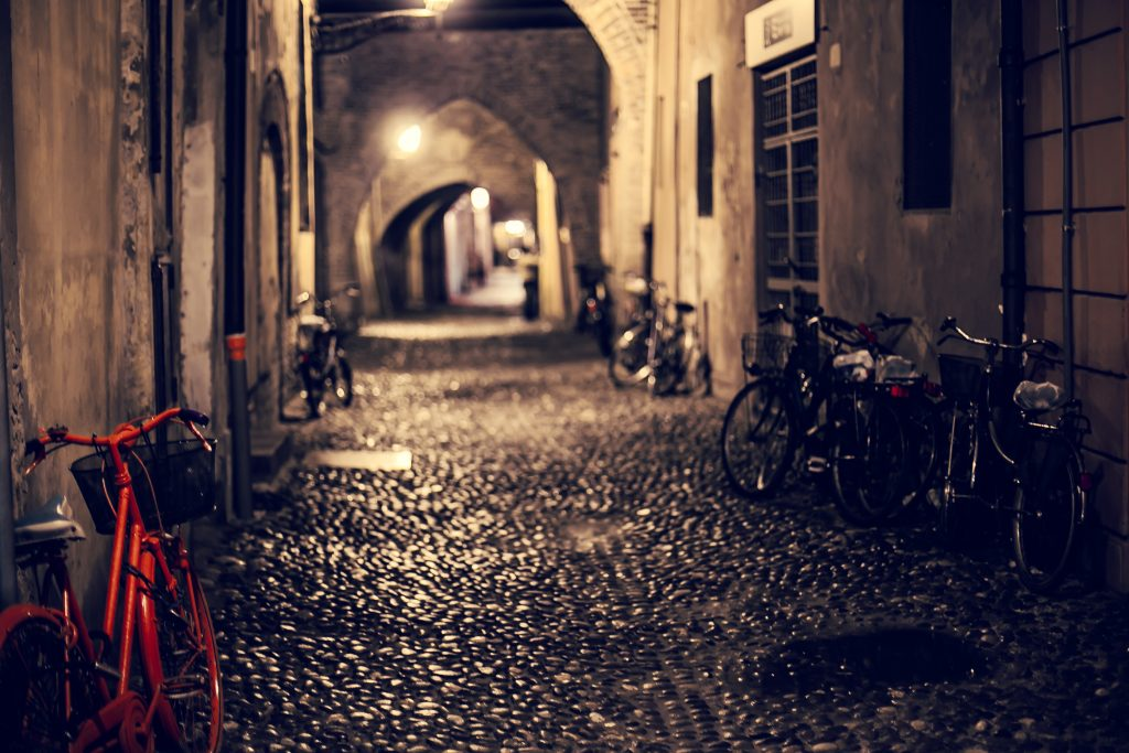 Bicycles in Via delle Volte by night, Ferrara, Italy.