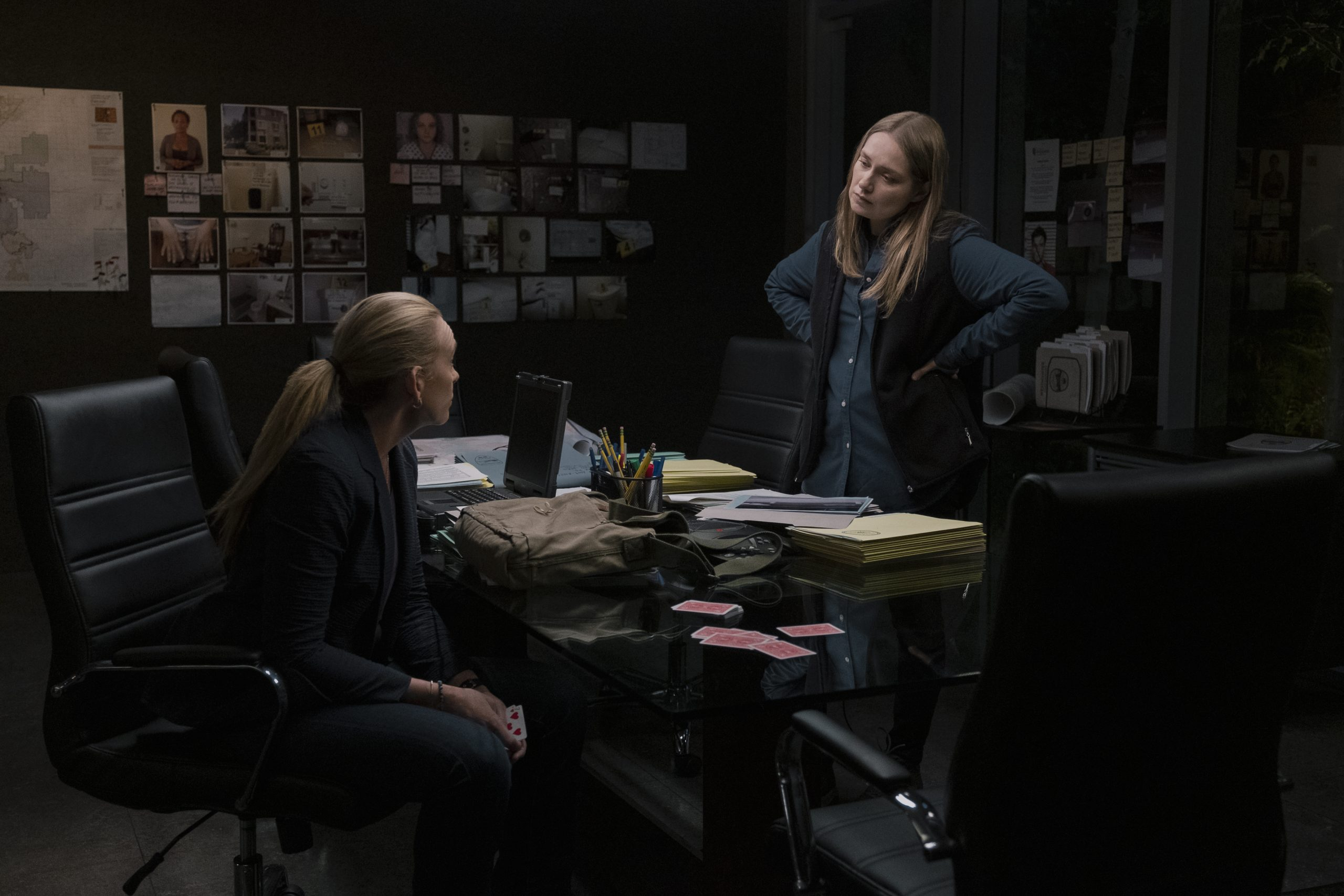 A woman is sitting at a desk inside an office and another woman is standing in front of her, discussing an investigation case