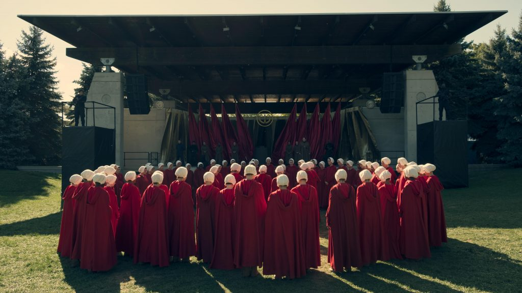 Offred and the Handmaids, in a white bonnet and a red cloak, are gathered in the open under a stage, where the Aunts complete the training