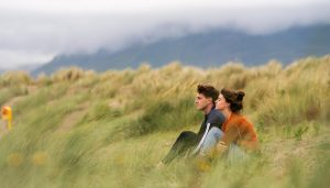 Normal People: Marianne and Connell sitting in the tall grass.