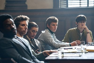 A production still from The Trial of the Chicago 7 featuring the defendants in the courtroom