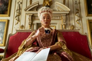 Bridgerton is a revolutionary period romance. The TV show aims to be a more inclusive version of a genre in which tradition is characterized by a predominance of white characters. The image shows Golda Rosheuvel as Queen Charlotte (based on real historical speculation regarding Queen Charlotte's African ancestry).