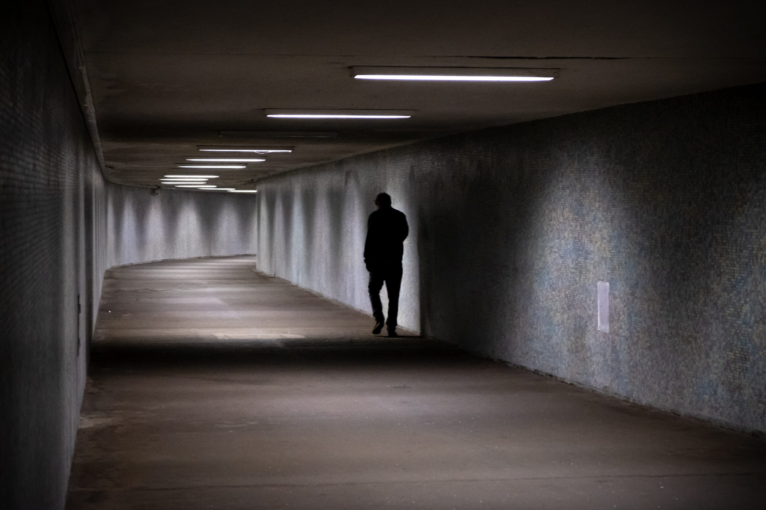 The Adversary | A True Story of Monstrous Deception - man walking in a dark grey tunnel