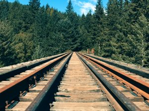 Stand by Me is a cult movie about the journey from childhood to adulthood. The image depicts old train tracks near a green forest. Train tracks are an essential point in the characters' journey.