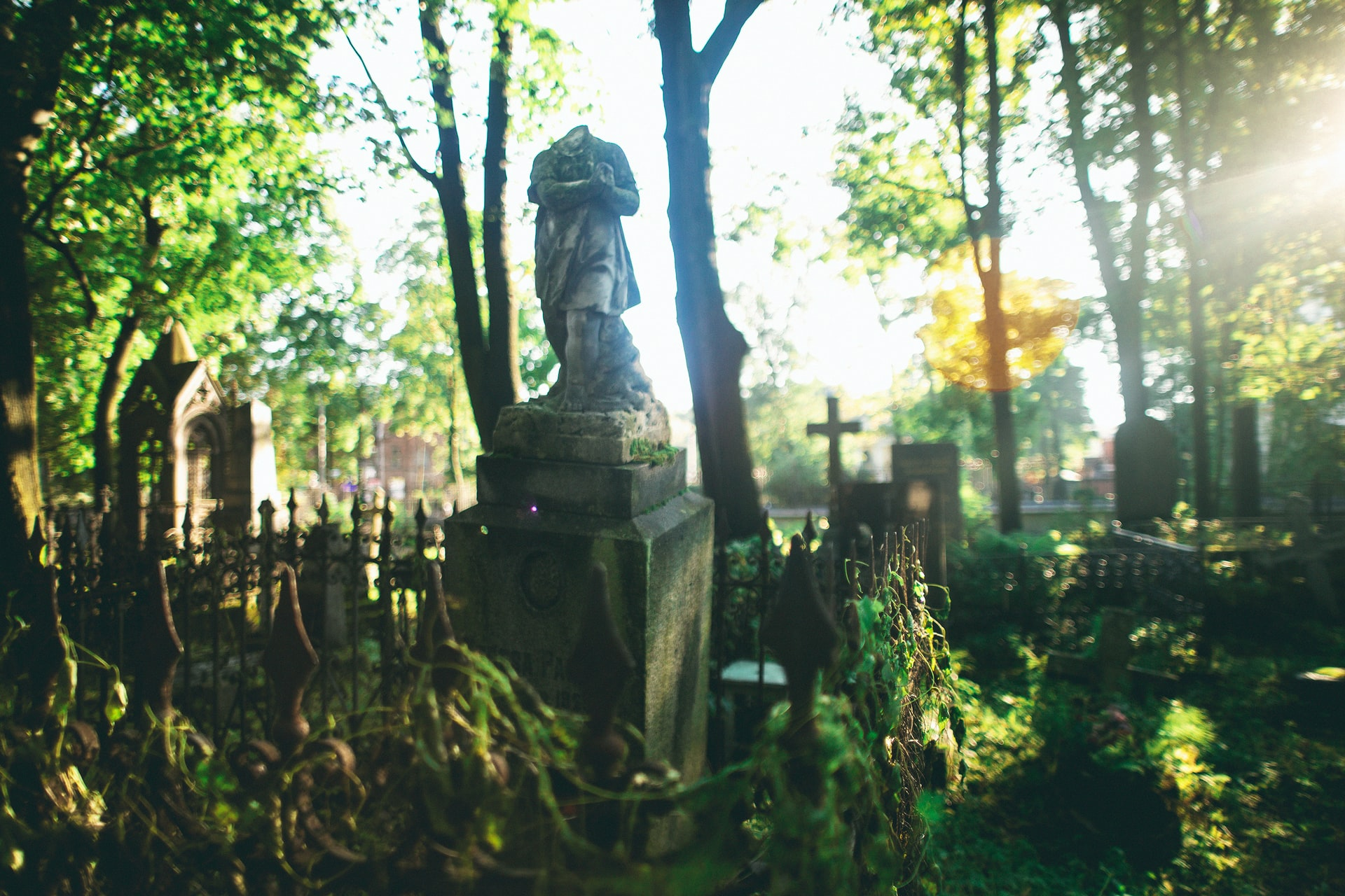 Garden of the Arcane Delights - The image shows a cemetery in the woods, thus some tree are visible together along with many tombs. At the center of the image, between two trees there is a headless statue