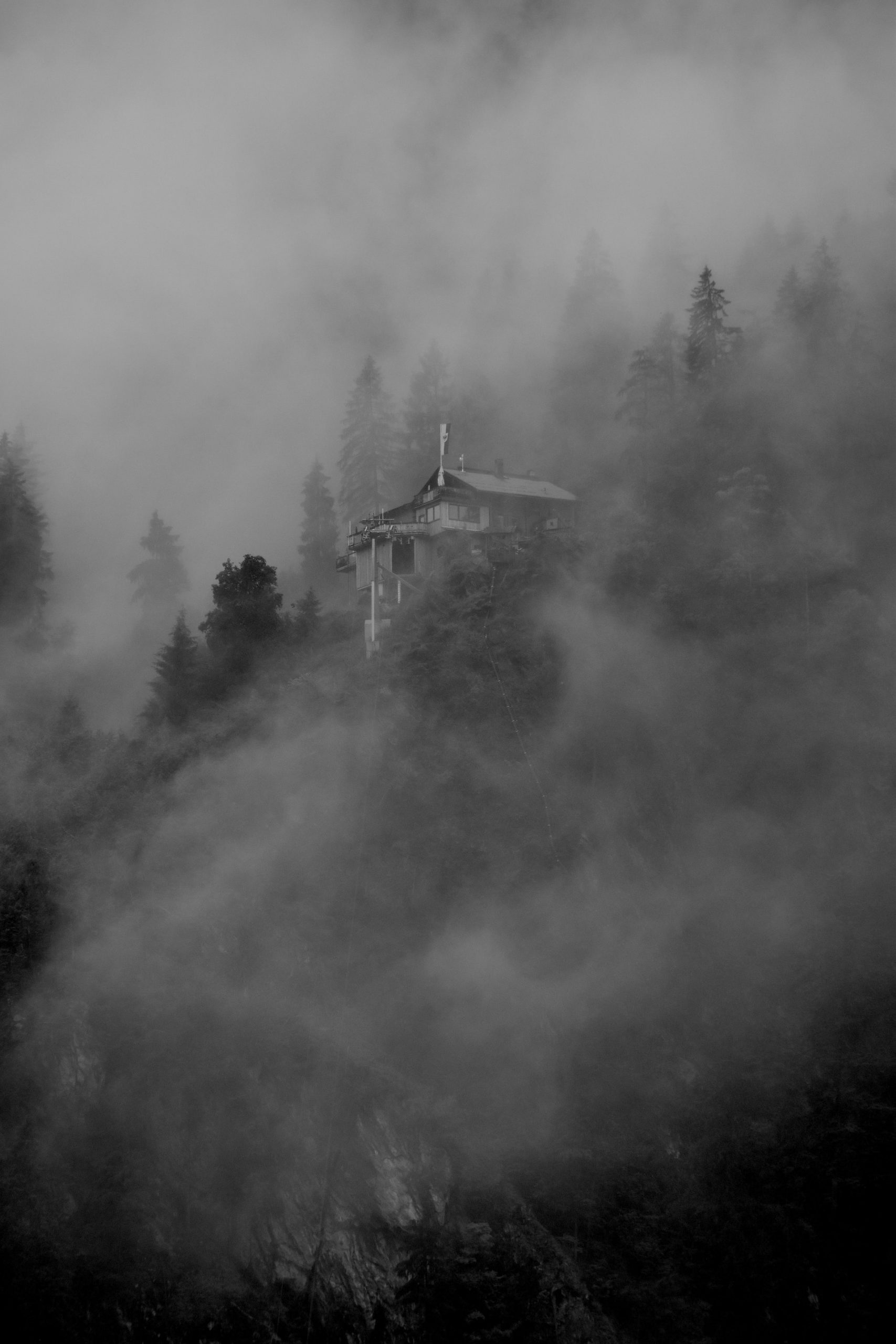 The image shows a house in a forest- like terrain shrouded by a mysterious fog. It suits the mood of the record