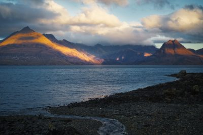 Windswept Adan - In this image we see a rocky shoreline and a piece of land in the distance with some mountains