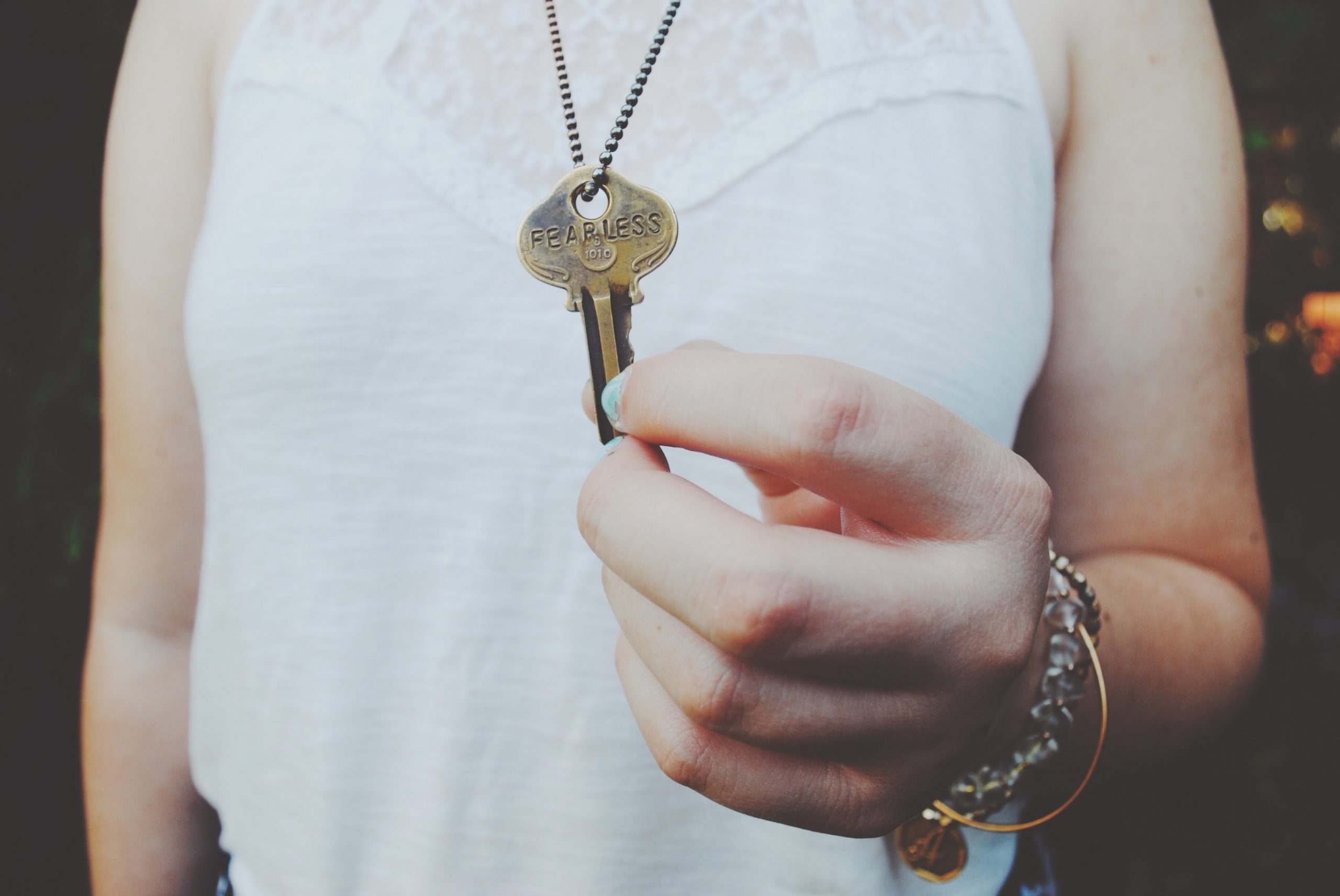 Fearless - A woman holding a key with the word fearless engraved