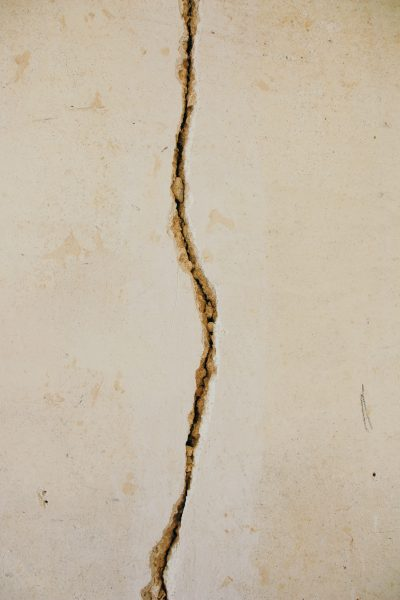 Cambiar de Idea | A woman and her scars - A white wall split in two by a crack