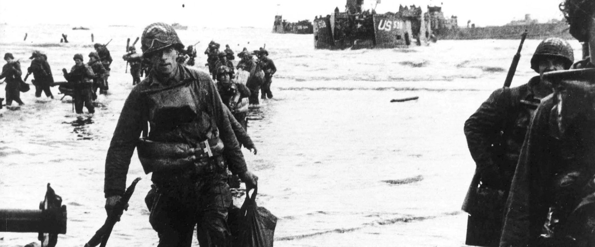 Carrying a full equipment, American assault troops move onto Utah Beach on the norther coast of France. Landing craft, in the background, jams the harbor. 6 June 1944.